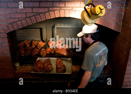 A worker pulls cooked pork ribs off the barbecue pit at a Dreamland Bar-B-Que Ribs restaurant in Birmingham, Alabama, - Stock Photo