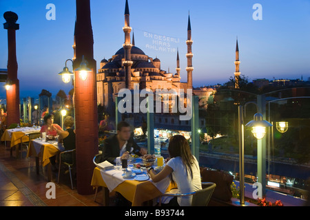 The Blue Mosque or Sultan Ahmet Mosque 1609 1616 rooftop restaurant dusk Sultanahmet District Istanbul Turkey - Stock Photo