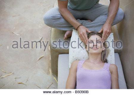 Man giving woman head massage - Stock Photo