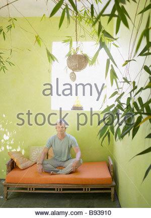 Man meditating on patio bench - Stock Photo
