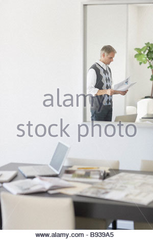 Man reviewing design paperwork at home - Stock Photo