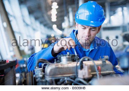 Technician working in auto shop - Stock Photo