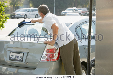 Man washing car window at service station - Stock Photo