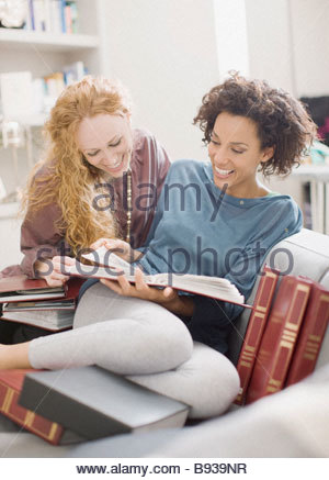 Women looking at photo albums - Stock Photo