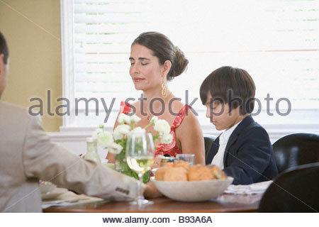 Family saying grace before dinner - Stock Photo