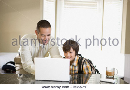 Father and son looking at laptop in kitchen - Stock Photo