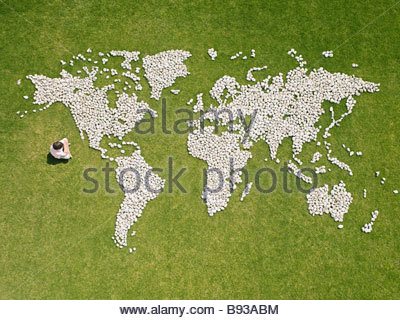 Boy sitting with world map made of rocks - Stock Photo