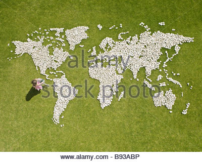 Girl watering world map made of rocks - Stock Photo