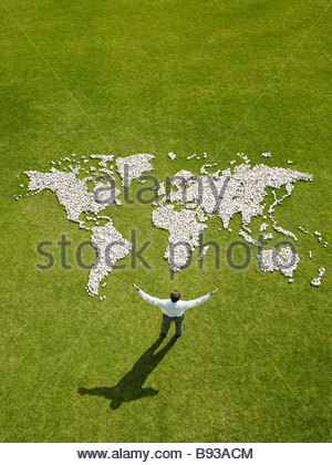 Businessman standing near world map made of rocks - Stock Photo