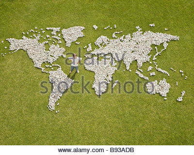 Boy standing in world map made of rocks - Stock Photo