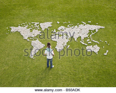 Father and daughter looking at world map made of rocks - Stock Photo