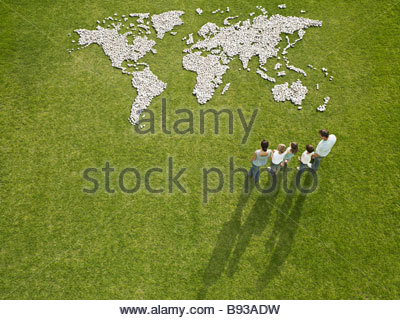 Family looking at world map made of rocks - Stock Photo