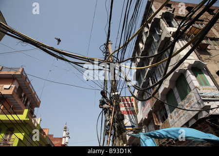 An electrician repairs cables on a pole in the street in Old Delhi, India. - Stock Photo