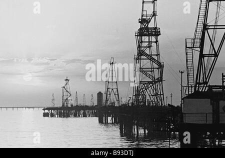 Sun rising above the oil drilling derricks of the Neftyanye Kamni Oil Stones offshore deposit near Baku Azerbaijan - Stock Photo