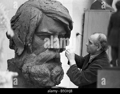 Sculptor Mikhail Anikushin a People s Artist of the USSR working on a bust of Vladimir Bekhterev - Stock Photo