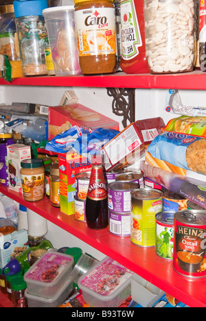 A cluttered untidy larder pantry housing lots of jars and tins etc. - Stock Photo