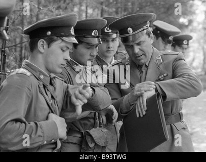 Cadets of the Moscow Mossovet Border Guards Command Higher School of the USSR KGB synchronizing watches before fulfilling - Stock Photo