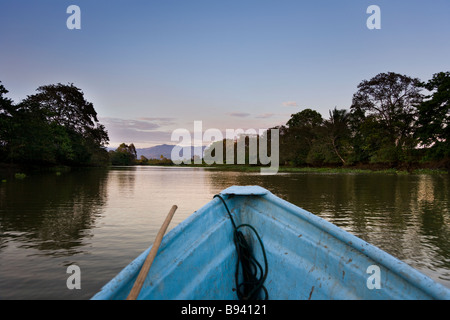 A boat going down the Sierpe River, gateway to Costa Rica's Corcovado National Park, with mountains in the background - Stock Photo