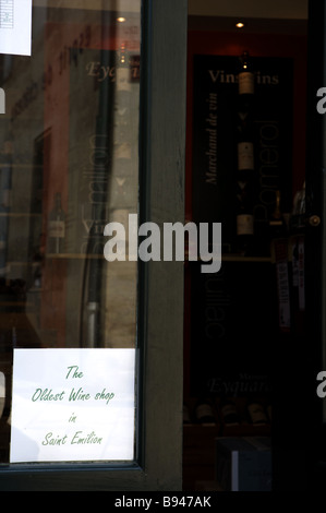 A sign in a shop window stating the oldest Wine shop on St Emilion The picturesque village of St Emilion Bordeaux - Stock Photo
