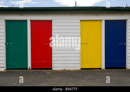 Four old multicoloured timber doors in red yellow green and blue - Stock Photo