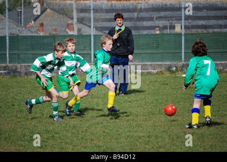 young boys playing football,uk - Stock Photo