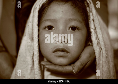 Annapurna Nepal 19 March 2008 Portrait of young gurung girl with mother holding chin in trekker logdge on the himalaya - Stock Photo