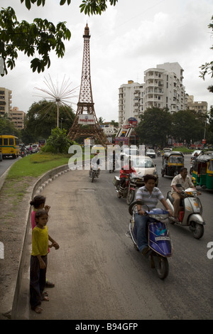 Indian children wait to cross the road near Parle Point roundabout in Surat, Gujarat. India. (Tower is based on - Stock Photo