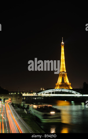 Night time view of the Eiffel Tower with red light trails from passing traffic and a ferry docking - Stock Photo