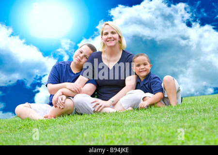 Pretty mom with her two sons outside on grass - Stock Photo