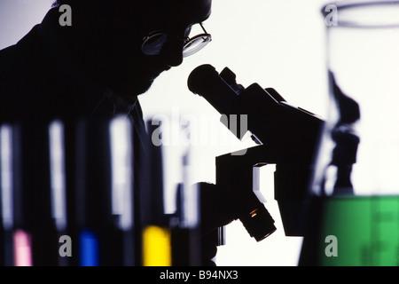 Chemistry apparatus, phamecutical prodution, scientist examines results in microscope - Stock Photo