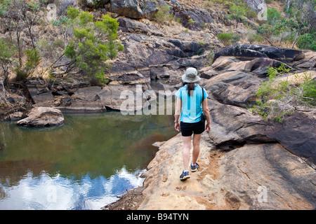 A woman in her mid 20s bushwalking through Australian bushland. Serpentine National Park, Perth, Western Australia - Stock Photo