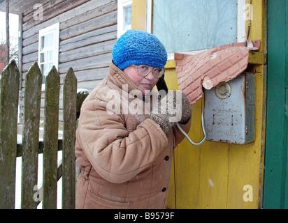 Woman uses public telephone at village headwoman s house Kirkovo village in the Leningrad Region s Tosno District - Stock Photo
