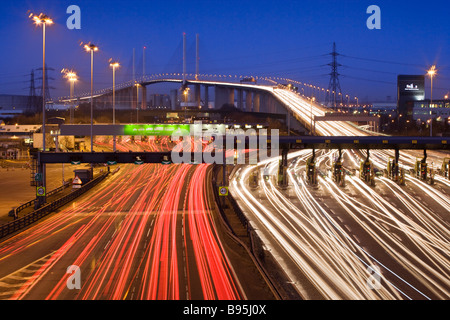 Traffic passing through toll booths at night. Queen Elizabeth II Bridge and Dartford Tunnel, Kent, UK - Stock Photo