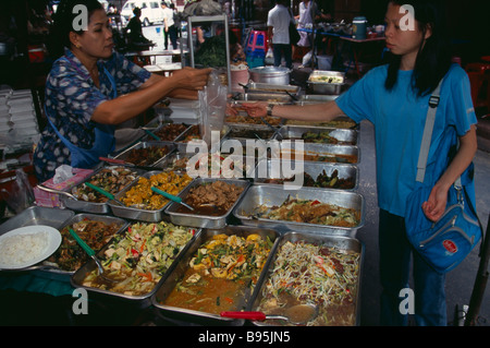 THAILAND South Bangkok Woman selling cooked food to a local woman in an alley beside Patpong 1 - Stock Photo