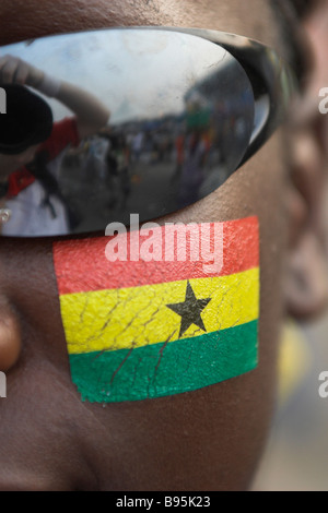 Face painting of Ghanaian flag on Ghana fan in Accra for opening game of Africa Cup of Nations - Stock Photo