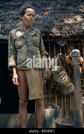 Vietnam War Central Highlands Montagnard Hill Tribe Man standing next to thatched roof hut at Dak Pek Special Forces - Stock Photo
