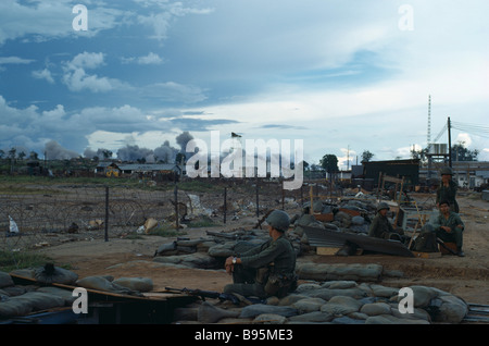 Vietnam War Central Highlands Siege of Kontum American B-52 bombing behind Kontum with Montagnard Soldiers sitting - Stock Photo