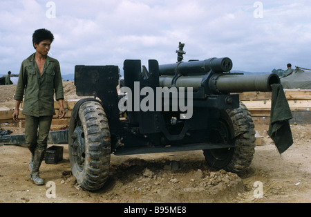 Vietnam War Central Highlands Siege of Kontum Montagnard hill tribe soldier next to a howitzer artillery cannon - Stock Photo