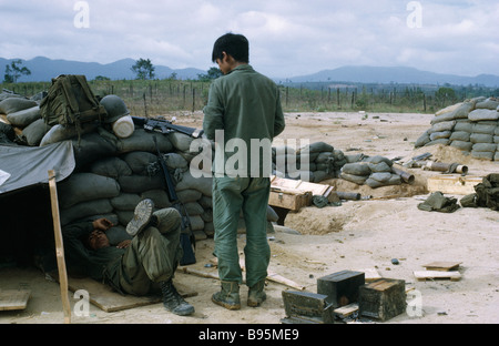 Vietnam War Central Highlands Siege of Kontum Montagnard Hill Tribe soldiers in camp with sand bags and makeshift - Stock Photo
