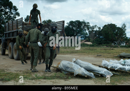 Vietnam War Central Highlands Siege of Kontum Montagnard soldiers wearing gas masks unloading dead bodies wrapped - Stock Photo