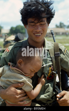 VIETNAM War Central Highlands Siege of Kontum Montagnard soldier carrying young child - Stock Photo
