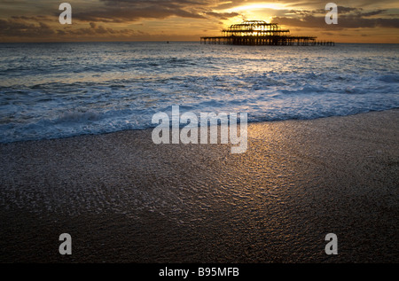 evening setting sun behind the remains of  the West Pier off the seashore at Brighton Sussex UK - Stock Photo