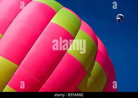 Switzerland, Canton de Vaud, Chateau d'Oex, part view of hot air balloon on ground as another balloon ascends behind. - Stock Photo