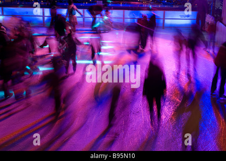 Germany, Bavaria, Munich. Ice skaters in motion blur with multi coloured light on a Winter ice rink in the city - Stock Photo