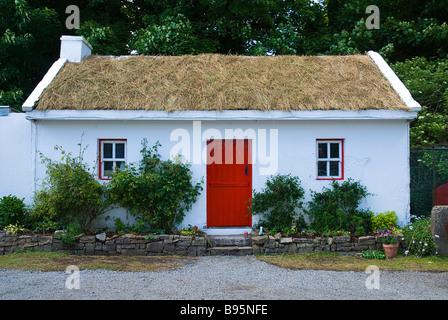 Ireland, County Sligo, Riverstown. White painted cottage at Sligo Folk Park thatched with turf. - Stock Photo