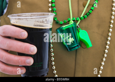 USA Colorado St Patrick's Day Detail of man wearing various green items whilst holding pint of stout beer in a plastic - Stock Photo