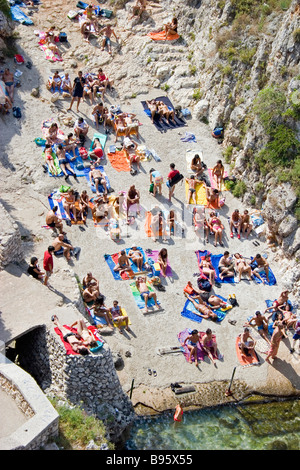 ITALY Puglia Lecce Tricase. Looking down on people sunbathing on coloured beach towels laid out on rocks next to - Stock Photo