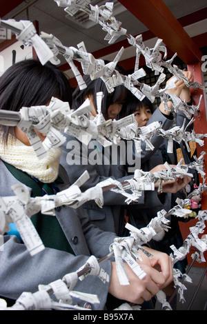 JAPAN Honshu Tokyo Asakusa Kannon or Senso-ji Shinto Temple Japanese female students hanging their omikuji fortune - Stock Photo