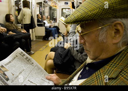 JAPAN Honshu Tokyo Tokyo Metro Elderly Japanese man wearing tweed cap and jacket reading a newspaper - Stock Photo