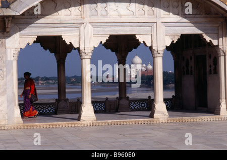 INDIA Uttar Pradesh Agra Taj Mahal seen through covered, colonnaded walkway with woman wearing red and purple sari - Stock Photo
